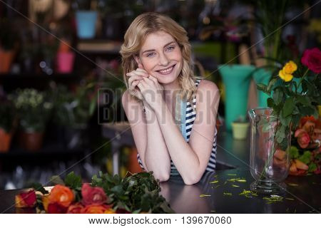 Portrait of happy female florist leaning in flower shop