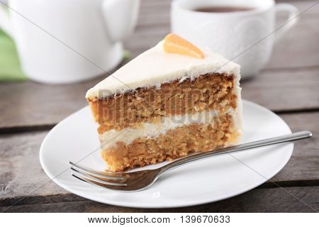 Delicious carrot cake with fork on wooden table