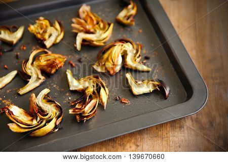Baked artichokes with spices on a baking tray