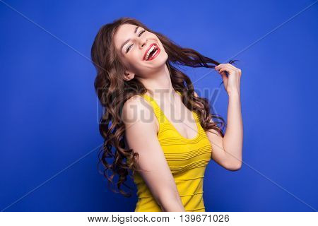 Portrait of smiling brunette girl with eyes closed pulling her long wavy hair.Isolate