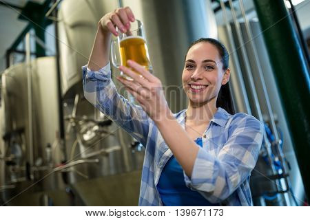Portrait of happy female brewer testing beer at brewery