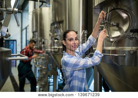 Portrait of female maintenance worker examining brewery machine at brewery