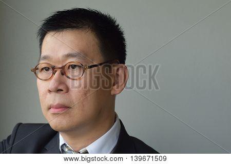 A sad looking asian business man looking afar