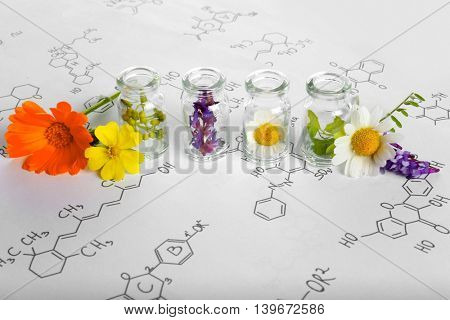 Different healing flowers in small glass bottles on paper with chemistry formula