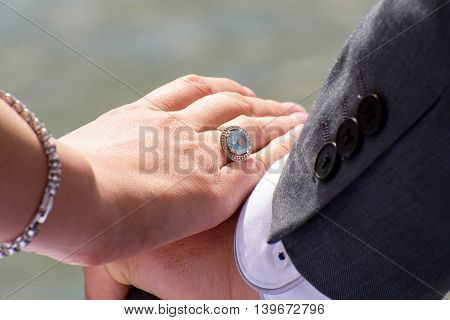 female hand caresses a man's hand on a background of water