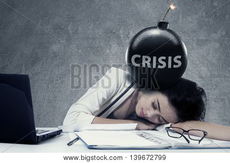 Young businesswoman sleeping on desk with a text of Crisis on the bomb at her head