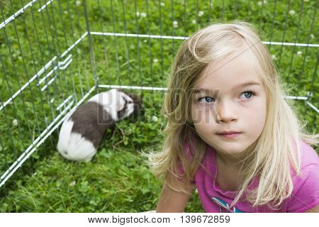 Child Girl inside paddock relaxing and playing with her guinea pigs outside on green grass lawn in the garden