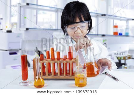 Little girl wearing coat and glasses while doing chemical research in the laboratory