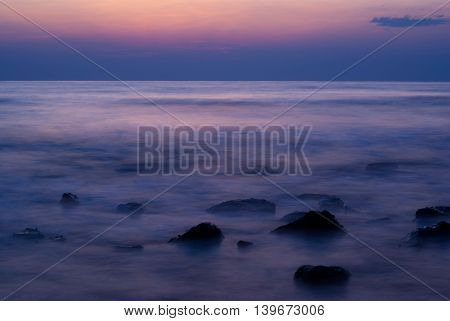 Soft waves on a rocky beach in the evening