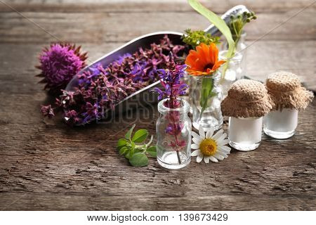 Composition with healing flowers and small glass bottles on wooden background