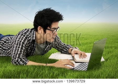 Male college student studying with notebook computer and book while lying down on the grass in nature