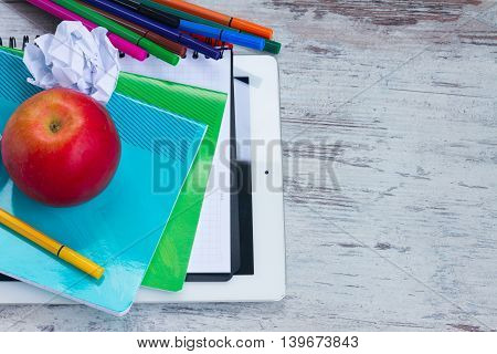 Red apple with school supplies on white wooden table
