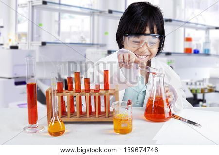 Photo of a little girl doing chemistry research while wearing glasses and coat in the library
