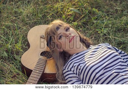 Hippie-style girl posing with a guitar on a hot summer evening she is wearing a head band stripy frock and skinny jeans