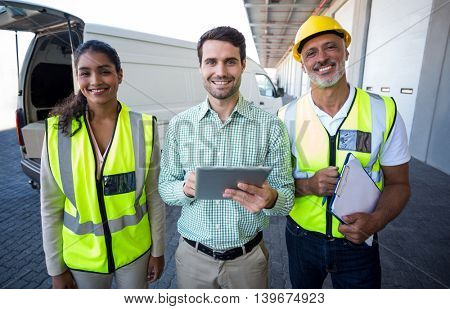 Manager and workers are smiling and posing face to the camera in front of a warehouse