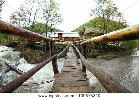 Old wooden bridge over the mountain stream