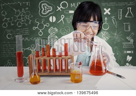 Photo of a little student makes chemical experiments in the lab with doodles on the blackboard