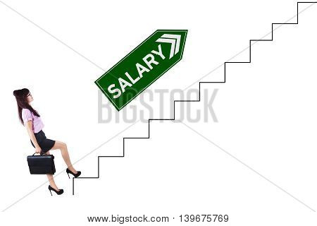 Photo of a pretty female worker walking on the stairs with salary text on the signpost
