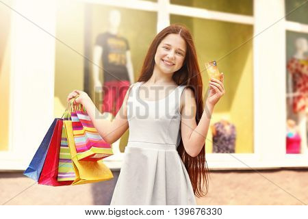 Beautiful girl with shopping bags on street