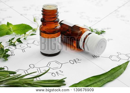 Dropper bottles and herbs on chemical formulas background