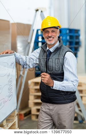 Smiling men holding a pen while looking at camera in warehouse