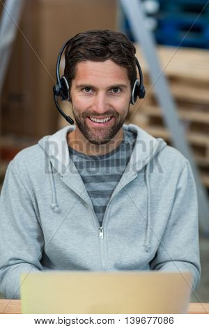 Portrait of a smiling worker wearing a headset with mic