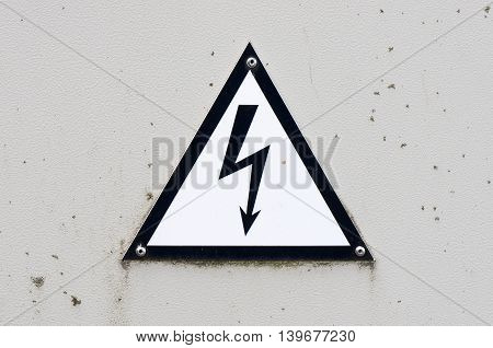 Old and dirty high voltage sign on white metal plate