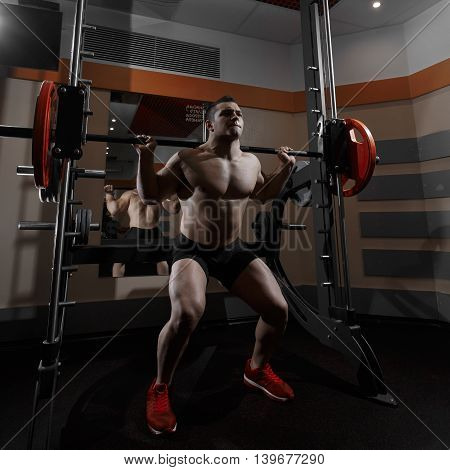 Fitness man doing squats with the barbell at the gym.