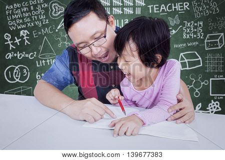Portrait of teacher guide a little girl to learn and write on the book shot with doodles background on chalkboard