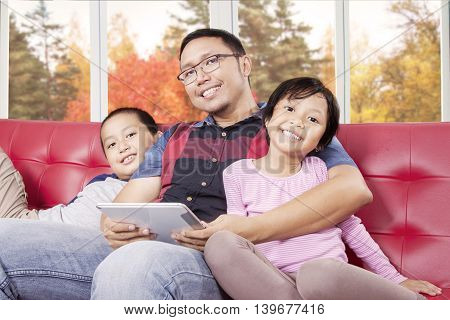 Portrait of two happy children and their father smiling at the camera while holding tablet on the sofa