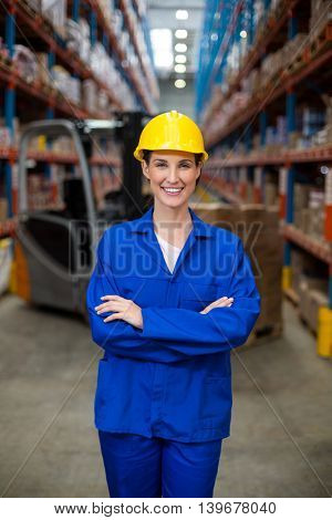 Female worker standing in front of camera in warehouse