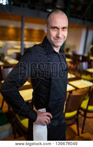 Portrait of happy waiter standing with hands on hip in resturant