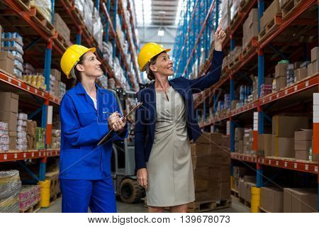 Female smiling coworkers looking up in warehouse