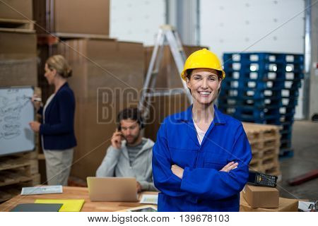 Female worker looking at camera while his colleague are working in the background in warehouse