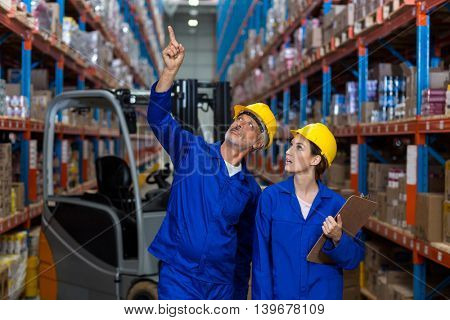 Coworkers looking up in warehouse