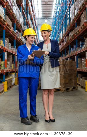 Standing female coworkers smiling to camera