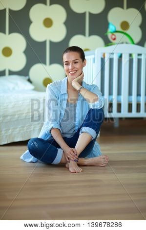 Young woman sitting on the floor near children's cot.