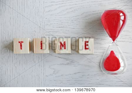 Word TIME with hourglass on wooden background