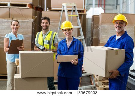 Smiling workers carrying boxes in warehouse