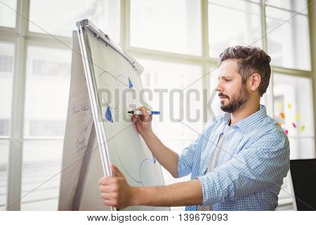 Young businessman drawing diagram on whiteboard in creative office