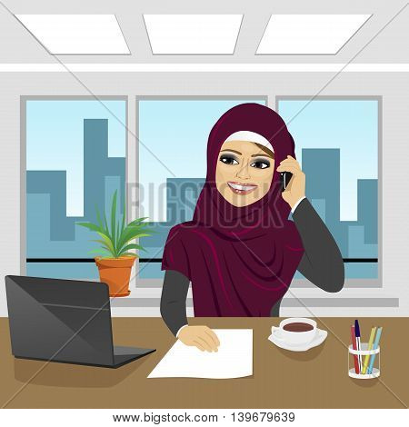 business arab woman with laptop at office wearing hijab talking on the phone