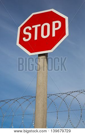 Bright red stop sign against blue sky and razor wire coil