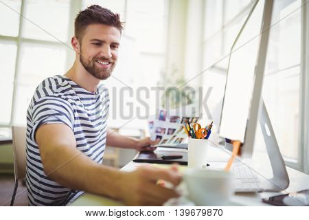 Happy businessman taking coffee cup at desk in creative office