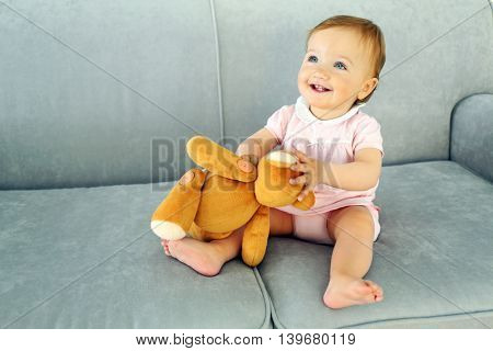 Baby sitting with teddy bear on sofa in room