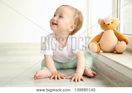 Baby sitting with teddy bear at window in room