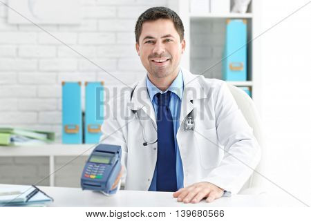 Pediatrician with credit card terminal at his office