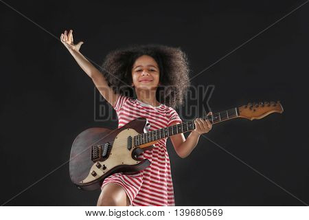 Afro-American little girl with curly hair playing guitar on dark background