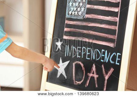 Boy pointing on chalk drawing of American flag on blackboard