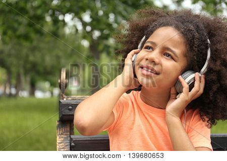 Afro-American little girl listening to music on bench in park