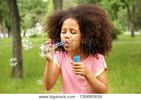 Afro-American little girl blowing soap bubbles
